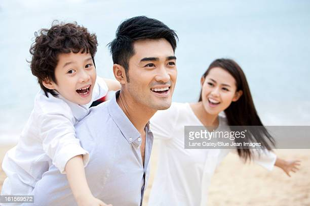 Merry young family relaxing on the beach of Repulse Bay, Hong Kong