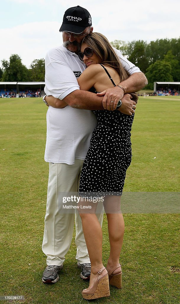 Merv Hughes and Elizabeth Hurley share a cuddle during the Shane Warne's Australia vs Michael Vaughan's England T20 match at Circenster Cricket Club on June 9, 2013 in Cirencester, England.