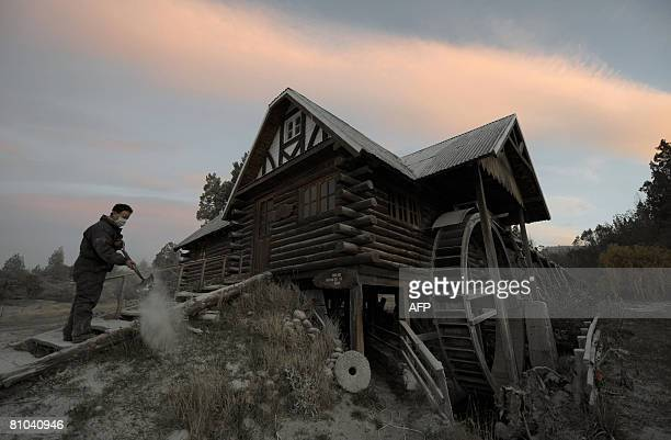 Mervyn Evans removes ashes of the Chaiten volcano in neighbouring Chile from his waterwheel a tourist spot near the border town of Los Cipreses in...