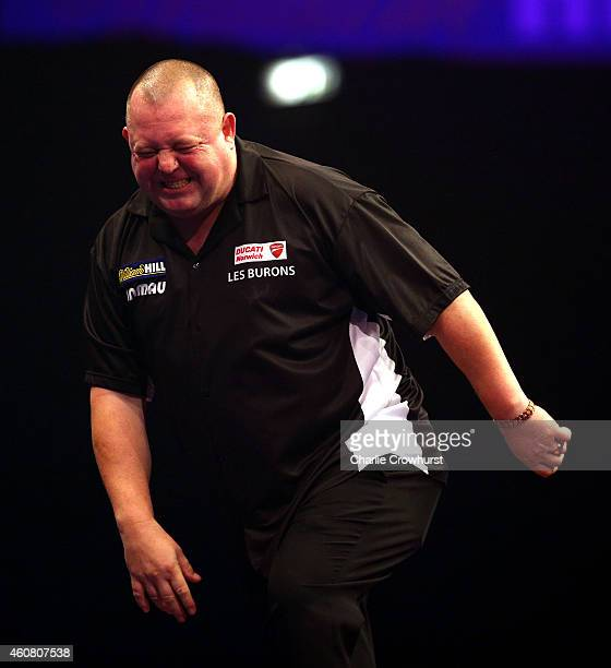 Mervyn King of England shows his pain as he plays with a bad back during his first round match against Max Hopp of Germany during the William Hill...