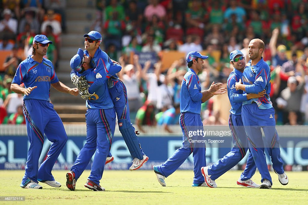 Merwais Ashraf of Afghanistan (R) celebrates with team mates after taking the wicket of Tamim Iqbal of Bangladesh during the 2015 ICC Cricket World Cup match between Bangladesh and Afghanistan at Manuka Oval on February 18, 2015 in Canberra, Australia.
