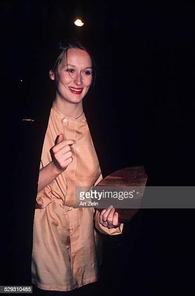 Meryl Streep wearing peach and carrying an award circa 1970 New York
