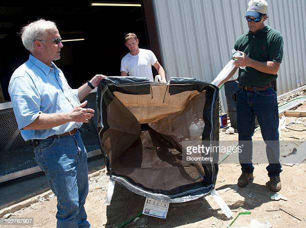 A meshlike porous polypropylene bag is held by Raymond Butler special project manager with British Petroleum Plc left and Jemison Marine owner Tim...