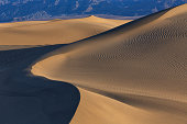 Waves of sand on top of the dunes at Sunrise in Mesquite flat dunes, Death Valley National Park, California, USA.