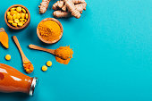 Mess of turmeric plant in different conditions: fresh, dry root, pills, powder and cut plant on blue background. Flat lay style. Place for text.