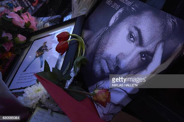 A message bearing a portrait of late British singer George Michael is seen amid flowers candles and other messages left by wellwishers in tribute...