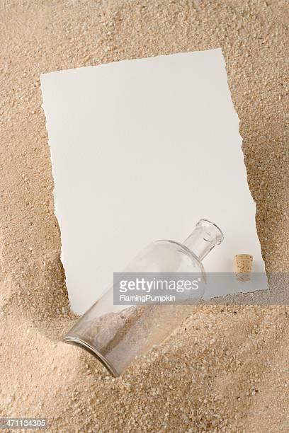 Message dans une bouteille sur la plage de sable.