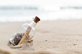 closeup of a glass bottle with a rolled message inside stranded in the sand of a lonely beach