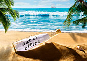 Message in a bottle with the note out of office on a beautiful tropical beach