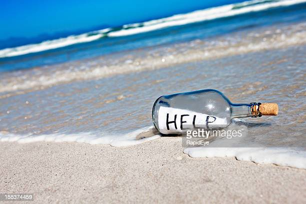 Message in bottle at waters edge says Help!