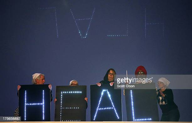 A message is displayed from the roof of the Sikh Temple of Wisconsin during a vigil to mark the oneyear anniversary of the shooting at the temple...