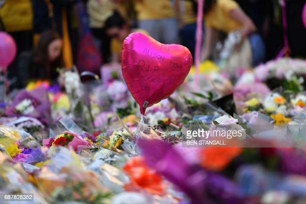 TOPSHOT A message on a balloon bobs amidst a carpet of flowers and messages at St Ann's Square in Manchester northwest England on May 24 placed in...