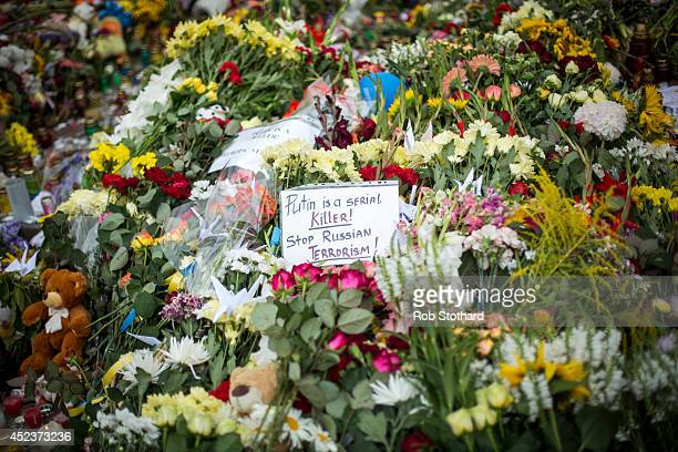 A message reading 'Putin is a serial killer Stop Russian terrorism' is left amongst floral tributes in front of the Netherlands Embassy in memory of...