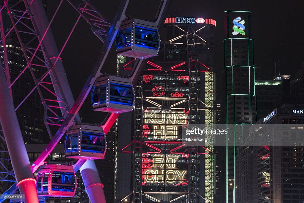 A message regarding the Chinese New Year is displayed on the HSBC Holdings Plc headquarters behind the Hong Kong Observation Wheel at night in Hong Kong, China, on Saturday, Feb. 13, 2016. HSBC's board will meet on Sunday to decide whether to shift its headquarters from London, according to two people with knowledge of the decision. Photographer: Xaume Olleros/Bloomberg via Getty Images