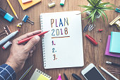 PLAN 2018 message with male hand writing on notepad paper on wooden table and office supplies.Business plan concepts.flat lay design