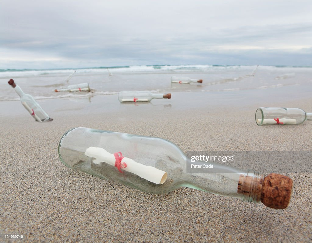 messages in bottles washed up on beach : Stock Photo