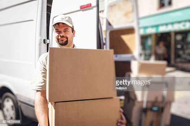 Messenger delivering parcel, standing next to his van