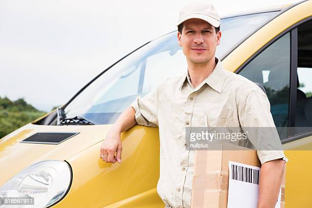 messenger with parcel standing next to his delivery van