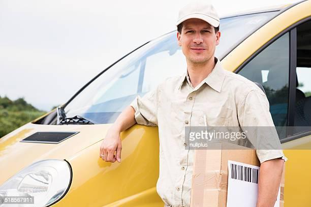 Bandoulière avec colis debout à côté de son Camionnette de livraison