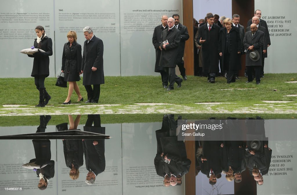"""Messina Weiss (L), 12, great grand-daughter of Holocaust survivor Gertrud Rocher, carries a flower as she leads diginitaries, including German President Joachim Gauck, his partner Daniela Schadt (both L), German Chancellor Angela Merkel (R) and Romani Rose (speaking with Merkel), Chairman of the Central Council of Sinti and Roma in Germany to the """"Memorial to the Sinti and Roma of Europe Murdered Under National Socialism"""" at the inauguration of the new memorial on October 24, 2012 in Berlin, Germany. In addition to targeting Jews during the Holocaust, Hitler also sought to exterminate the Roma population in Europe and estimates of the number killed range from 220,000 to 1,500,000."""