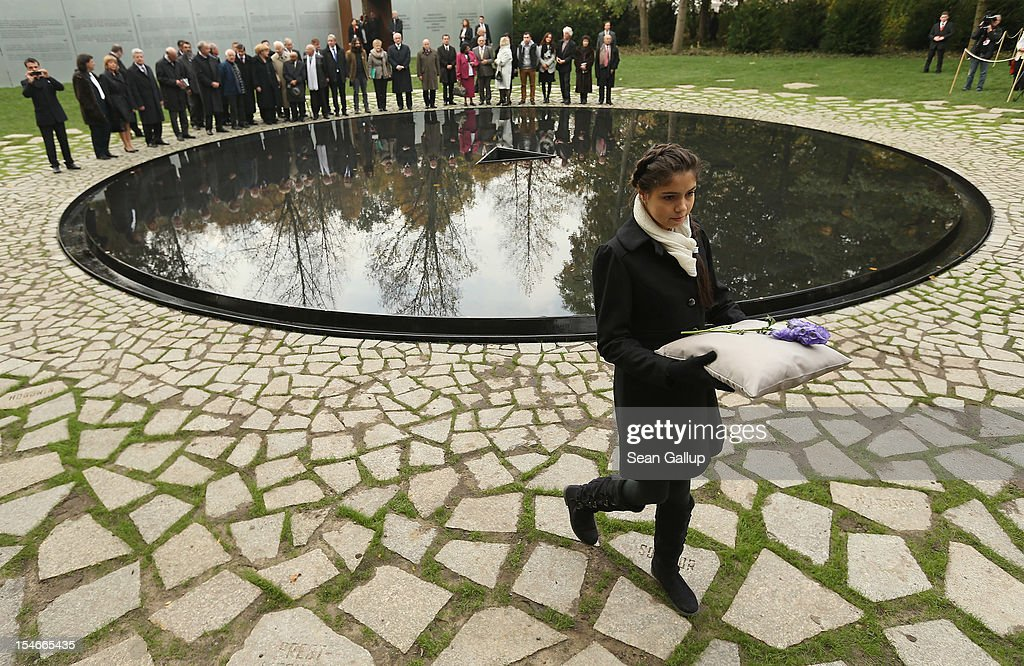 """Messina Weiss, 12, great grand-daughter of Holocaust survivor Gertrud Rocher, carries a flower past the """"Memorial to the Sinti and Roma of Europe Murdered Under National Socialism"""" at the inauguration of the new memorial on October 24, 2012 in Berlin, Germany. In addition to targeting Jews during the Holocaust, Hitler also sought to exterminate the Roma population in Europe and estimates of the number killed range from 220,000 to 1,500,000."""