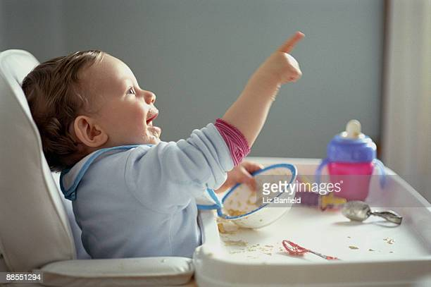 Messy boy in high chair pointing
