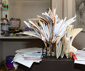 Example of desk clutter with haphazardly arranged, overstuffed file folders in a rack on a messy desk in a cluttered room. Canon EOS 5DIII, 35mm
