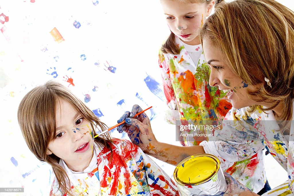 Messy Hispanic mother painting daughter's face : Stock Photo