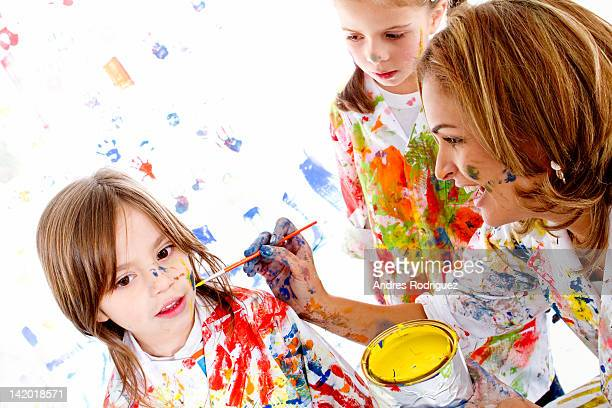 Messy Hispanic mother painting daughter's face