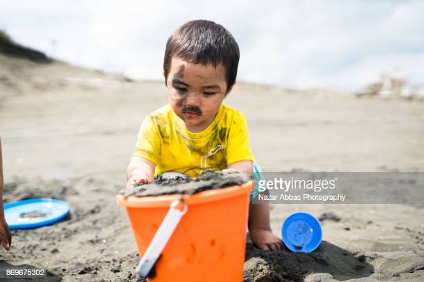 Messy kid at beach playing with sand.