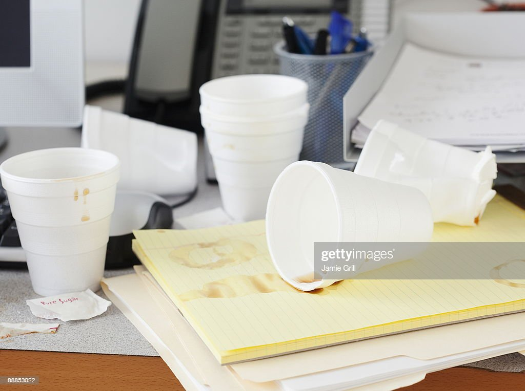 office cups. Messy Office Desk With Empty Disposable Cups Stock Photo