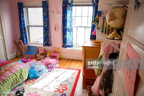 A messy pink girl's bedroom with toys and clothes on floor