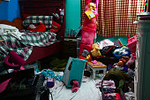 Young girl's unkept room filled with toys and clothes.