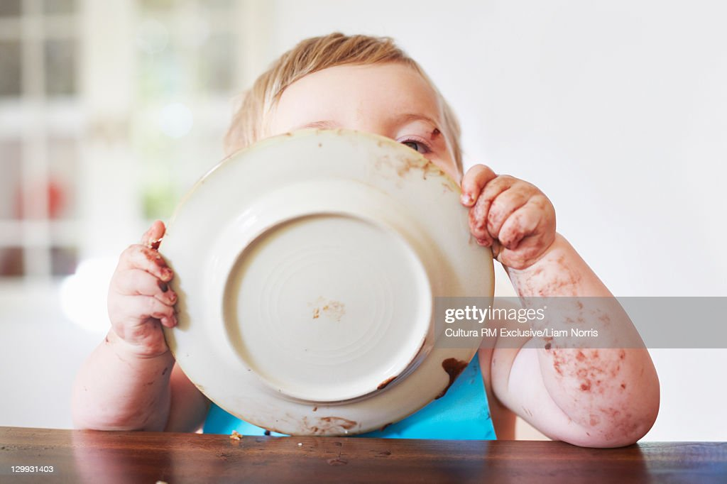 Messy toddler boy licking plate : Stock Photo