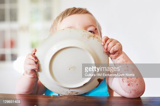 Messy toddler boy licking plate : Foto de stock