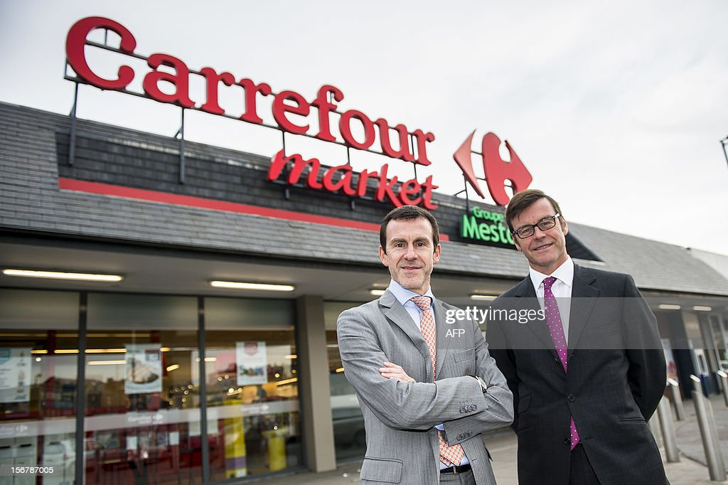 Mestdagh group CEO Eric Mestdagh and Mestdagh group CEO John Mestdagh pose in front of a 'Carrefour Market' in Couillet, Charleroi on November 21, 2012. 83 Champion supermarkets of the Mestdagh group changed names to 'Carrefour Market', which they say is a commercial strategy more than a change of identity. AFP PHOTO / BELGA / NICOLAS LAMBERT