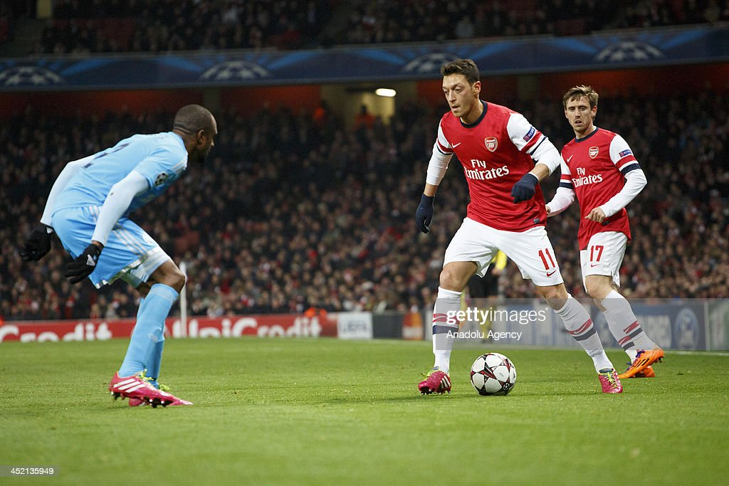 Mesul Ozil of Arsenal (R) vies for the ball during the UEFA Champions League group F football match between Arsenal and Olympique de Marseille at the Emirates Stadium on November 26, 2013 in London, England.