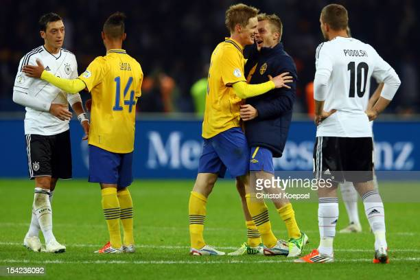 Mesut Oezil and Lukas Podolski of Germany look dejected and Rasmus Elm and Sebastian Larsson of Sweden celebrate after the 44 draw of the FIFA 2014...