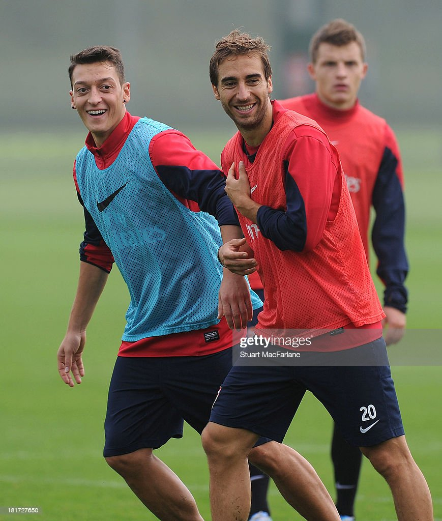Mesut Oezil and Mathieu Flamini of Arsenal during a training session at London Colney on September 24, 2013 in St Albans, England.