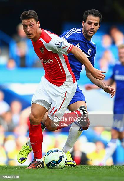 Mesut Oezil of Arsenal and Cesc Fabregas of Chelsea battle for the ball during the Barclays Premier League match between Chelsea and Arsenal at...