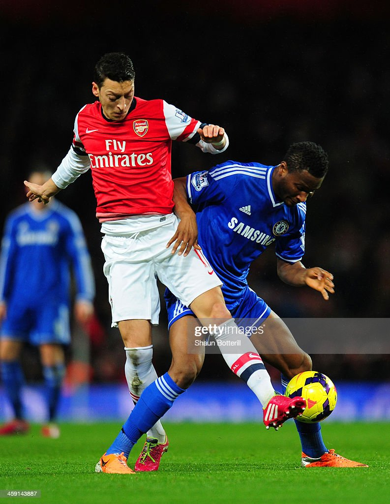 Mesut Oezil of Arsenal and John Obi Mikel of Chelsea compete for the ball during the Barclays Premier League match between Arsenal and Chelsea at Emirates Stadium on December 23, 2013 in London, England.