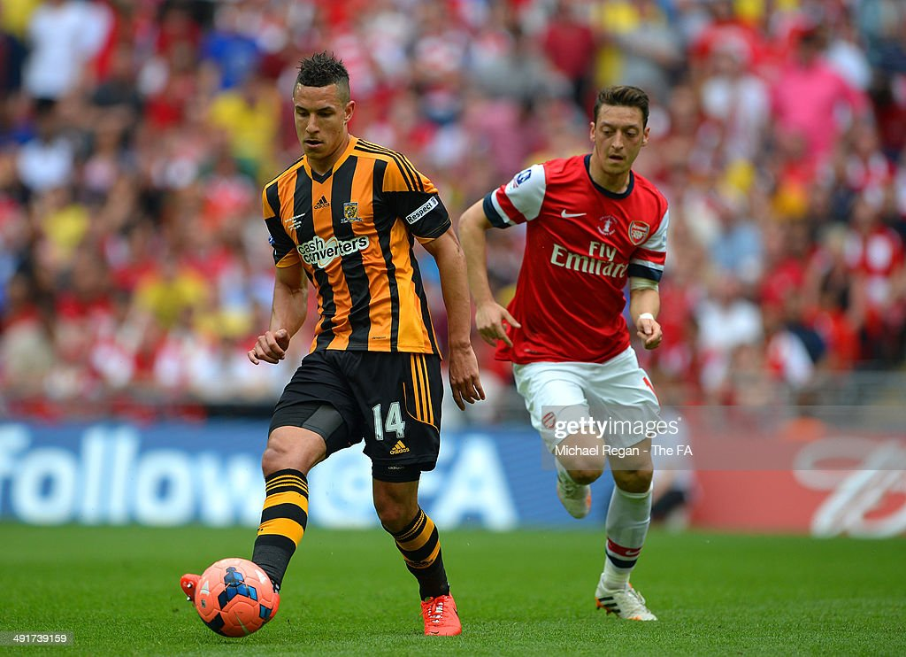 Mesut Oezil of Arsenal battles for the ball with Jake Livermore of Hull City during the FA Cup with Budweiser Final match between Arsenal and Hull City at Wembley Stadium on May 17, 2014 in London, England.