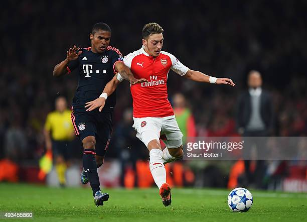 Mesut Oezil of Arsenal battles with Douglas Costa of Bayern Munich during the UEFA Champions League Group F match between Arsenal FC and FC Bayern...