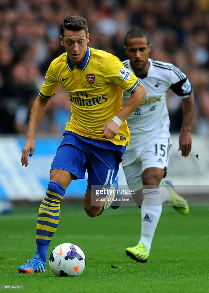 <a gi-track='captionPersonalityLinkClicked' href=/galleries/search?phrase=Mesut+Oezil&family=editorial&specificpeople=764075 ng-click='$event.stopPropagation()'>Mesut Oezil</a> of Arsenal breaks past <a gi-track='captionPersonalityLinkClicked' href=/galleries/search?phrase=Wayne+Routledge&family=editorial&specificpeople=206672 ng-click='$event.stopPropagation()'>Wayne Routledge</a> of Swansea during the Barclays Premier League match between Swansea and Arsenal at Liberty Stadium on September 28, 2013 in Swansea, Wales.
