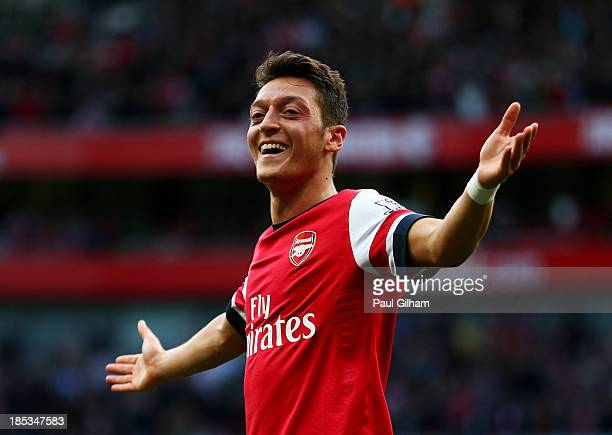 Mesut Oezil of Arsenal celebrates as he scores their second goal during the Barclays Premier League match between Arsenal and Norwich City at...