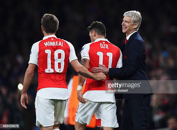 Mesut Oezil of Arsenal celebrates with team mate Nacho Monreal and Arsene Wenger manager of Arsenal as he scores their second goal during the UEFA...