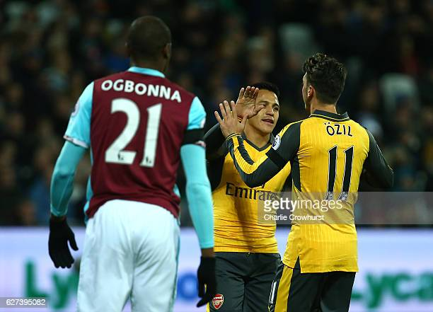 Mesut Oezil of Arsenal celebrates with teammate Alexis Sanchez after scoring the opening goal during the Premier League match between West Ham United...