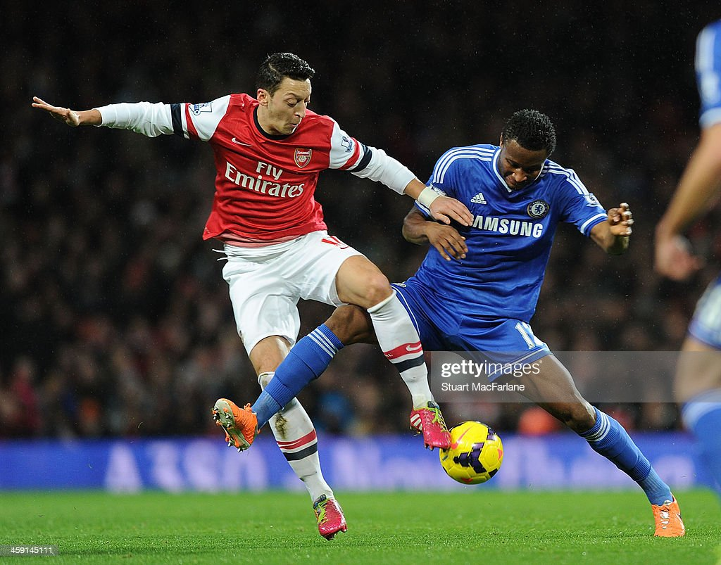 Mesut Oezil of Arsenal challenged by John Obi Mikel (R) of Chelsea during the match at Emirates Stadium on December 23, 2013 in London, England.