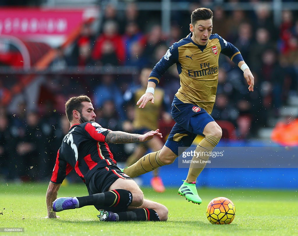 Mesut Oezil of Arsenal evades a tackle from Steve Cook of Bournemouth during the Barclays Premier League match between A.F.C. Bournemouth and Arsenal at the Vitality Stadium on February 7, 2016 in Bournemouth, England.
