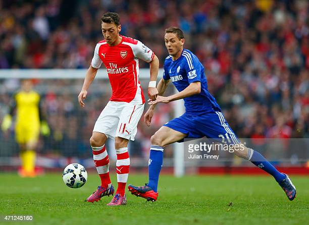 Mesut Oezil of Arsenal evades Nemanja Matic of Chelsea during the Barclays Premier League match between Arsenal and Chelsea at Emirates Stadium on...